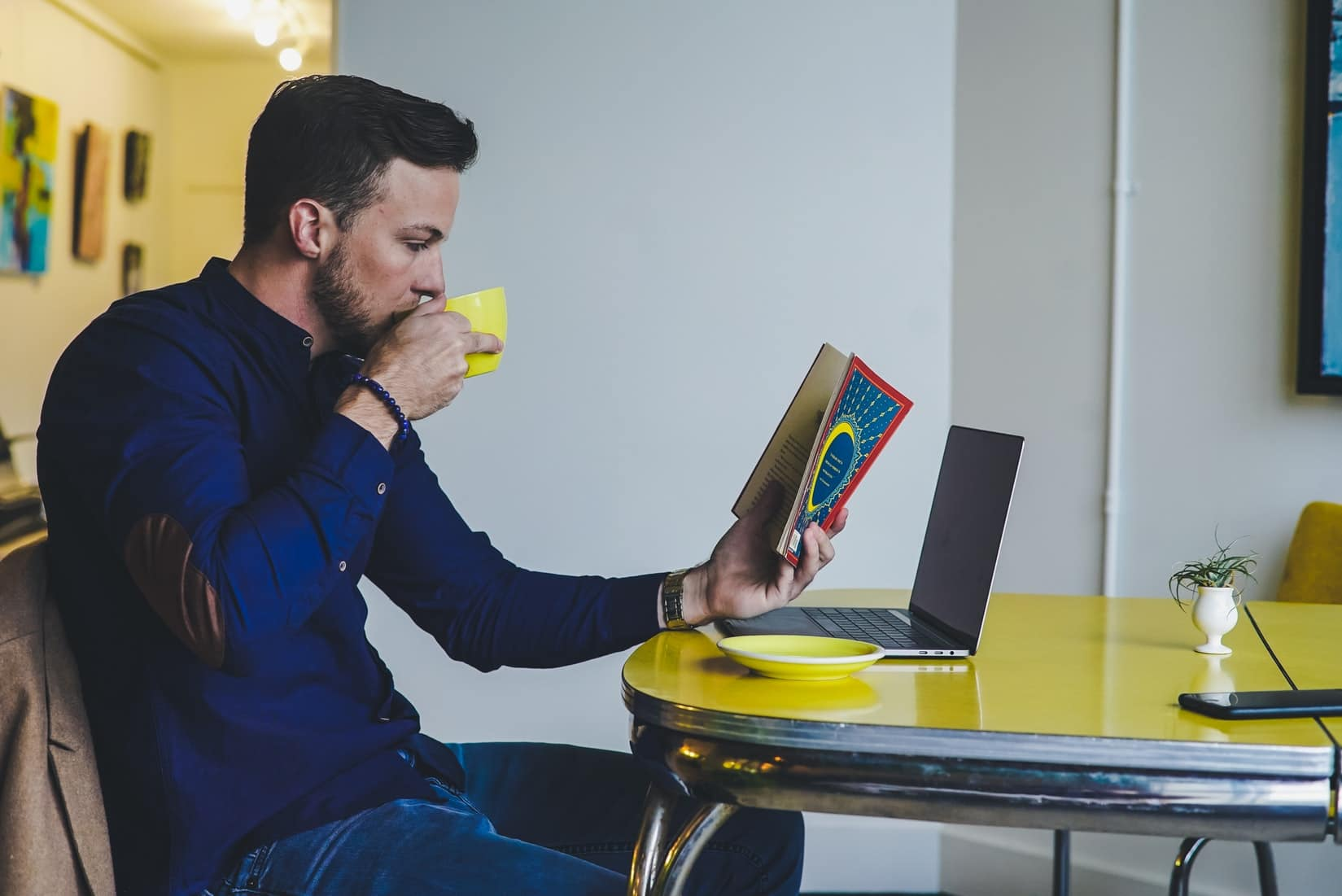 Man reading one of the best seduction books while drinking coffee.