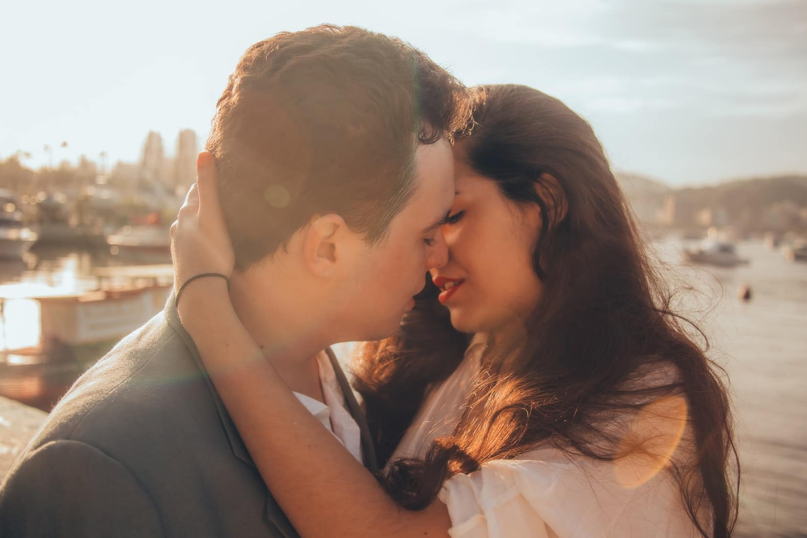 Guy kissing a girl as the sun sets.
