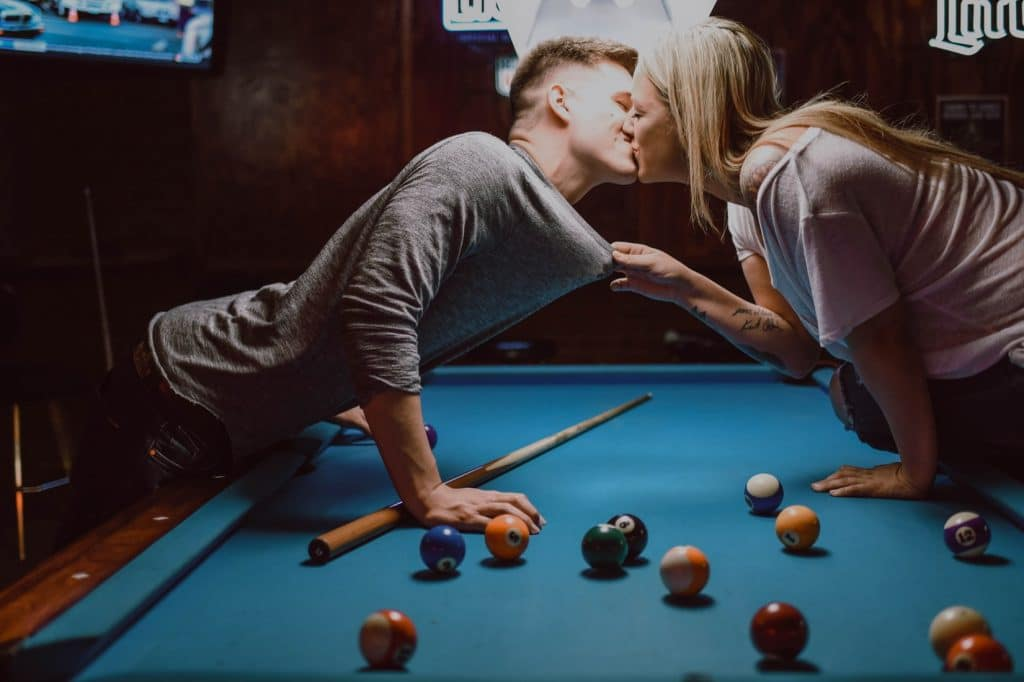 Woman kissing a guy over a pool table.