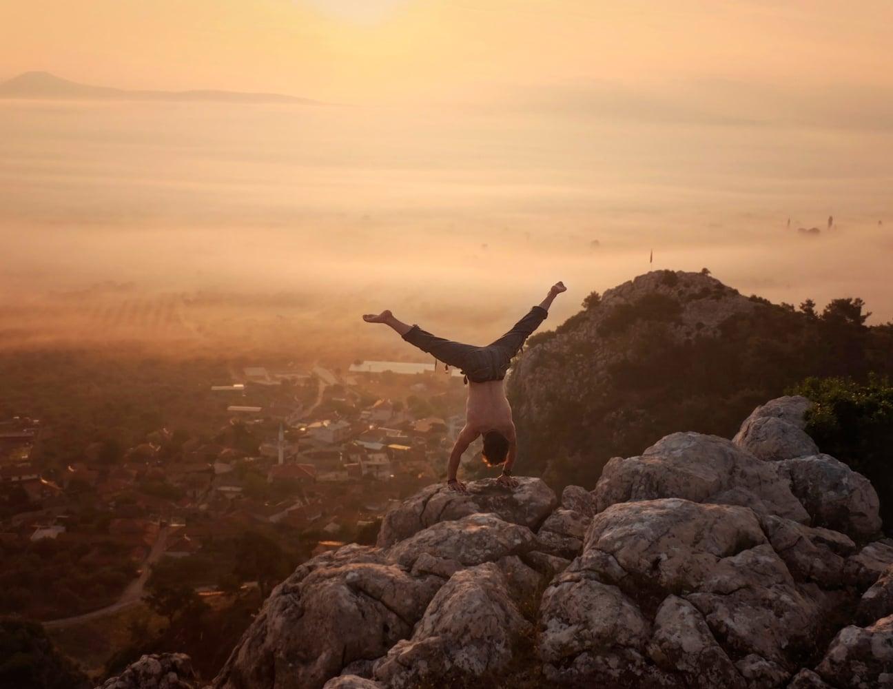 Man handstanding on a rock.